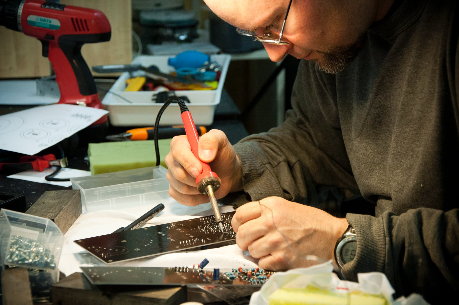 man while using a soldering iron