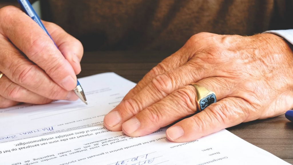 hands while signing a paper