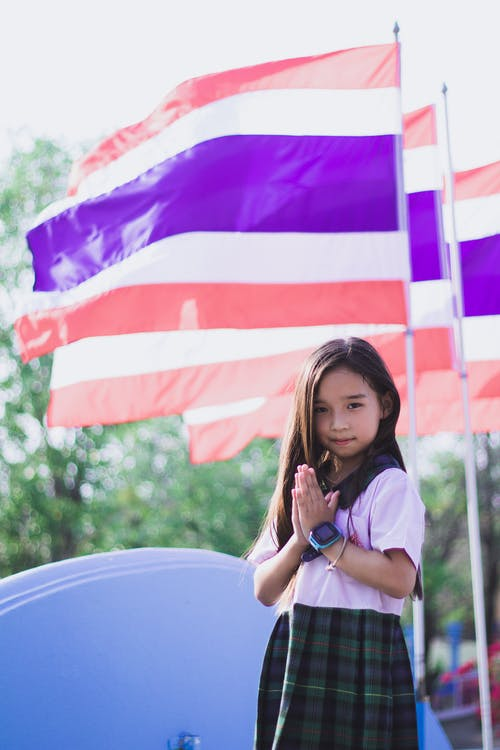 little girl in her uniform next to a flag
