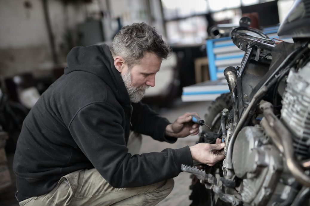 Mechanic using automotive workshop equipment